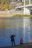 Молодая мать идет с ее ребенком вдоль банка реки Ural Стоковые Изображения RF