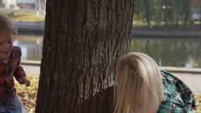 Молодая мать имея потеху с ее сыном в парке осени на солнечном дне видеоматериал