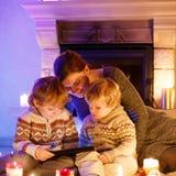 Молодая мать и его маленькие дети сидя камином на c Стоковое Фото