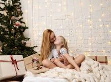 Молодая мать и ее дочери ittle лежа около волшебных подарков Нового Года рождественской елкой Стоковая Фотография RF