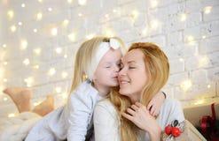 Молодая мать и ее дочери ittle лежа около волшебных подарков Нового Года рождественской елкой Стоковое фото RF