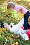 Молодая мать и ее дочь лежа на leav осени Стоковая Фотография