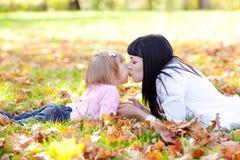 Молодая мать и ее дочь лежа на leav осени Стоковые Изображения