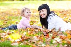 Молодая мать и ее дочь лежа на leav осени Стоковые Фотографии RF