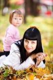 Молодая мать и ее дочь лежа на leav осени Стоковое Изображение