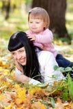 Молодая мать и ее дочь лежа на leav осени Стоковая Фотография RF