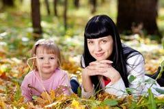 Молодая мать и ее дочь лежа на leav осени Стоковые Изображения RF