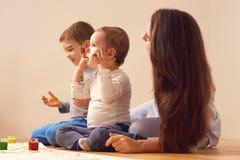Молодая мать и ее 2 маленьких сынов одетых в домашних одеждах сидят на деревянном поле в комнате и красить стоковое фото rf