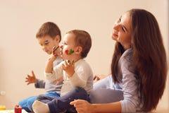 Молодая мать и ее 2 маленьких сынов с красками на их сторонах одетых в домашних одеждах сидят на деревянном стоковые изображения