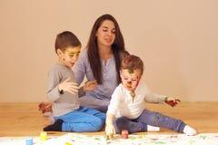 Молодая мать и ее 2 маленьких сынов с красками на их сторонах одетых в домашних одеждах сидят на деревянном стоковое изображение