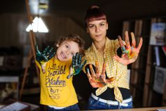 Молодая мать и ее сын играя с красками цвета в студии искусства стоковая фотография
