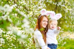 Молодая мать и ее уши зайчика дочери нося в саде весны на день пасхи Стоковые Фото