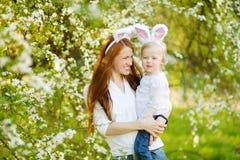Молодая мать и ее уши зайчика дочери нося в саде весны на день пасхи Стоковые Изображения