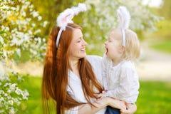 Молодая мать и ее уши зайчика дочери нося в саде весны на день пасхи Стоковое Изображение RF