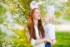 Молодая мать и ее уши зайчика дочери нося в саде весны на день пасхи Стоковая Фотография RF