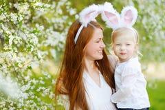 Молодая мать и ее уши зайчика дочери нося в саде весны на день пасхи Стоковое Изображение