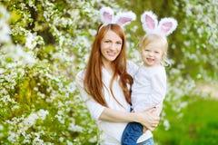 Молодая мать и ее уши зайчика дочери нося в саде весны на день пасхи Стоковые Изображения RF