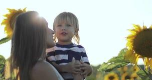 Молодая мать и мальчик стоят на поле с солнцецветами видеоматериал