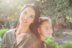 Молодая мать и милая девушка сидя спина к спине в природе в солнечном свете Стоковое Изображение RF