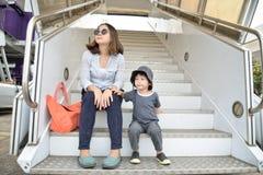 Молодая мать и сын сидя на лестницах восхождения на борт пассажира на стоковое фото rf