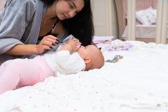 Молодая мать кормить ее младенца от бутылки стоковое изображение rf