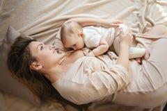 Молодая мать кормит ее ребенка грудью, держа ее в ее оружиях и усмехаясь от счастья ребенок 9 месяцев старый стоковые фотографии rf