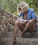 Молодая мать кормит ее newborn младенца грудью на лестницах Стоковые Изображения