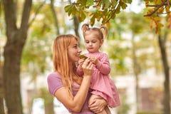 Молодая мать на прогулке с дочерью и лист в руках Стоковые Фотографии RF