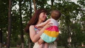 Молодая мать объезжая младенца в ее оружиях и смеясь над идти с ним в городе сток-видео