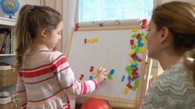 Молодая мать объясняя арифметику к милой маленькой дочери дома видеоматериал