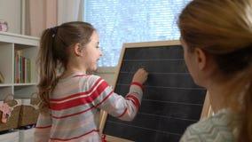 Молодая мать объясняя арифметику к милой маленькой дочери дома акции видеоматериалы
