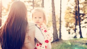 Молодая мать-одиночка держа милую дочь девушки малыша в ее оружиях и штрихуя ее волосы, концепцию силы девушки Стоковые Изображения