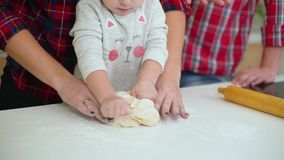 Молодая мать помогает ее маленькой дочери замешать тесто и отца наблюдая их видеоматериал