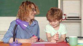 Молодая мать помогая его сыну сделать домашнюю работу Образование для детей внешкольных Зрачок исследования начальной школы сток-видео