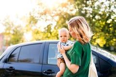 Молодая мать при ее маленький ребёнок готовя автомобиль Стоковые Изображения RF