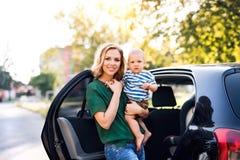 Молодая мать при ее маленький ребёнок готовя автомобиль Стоковое Изображение