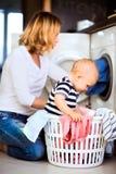 Молодая мать при ребёнок делая домашнее хозяйство Стоковое фото RF