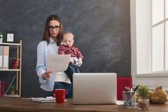 Молодая мать работая и тратя время с младенцем Стоковое Изображение RF