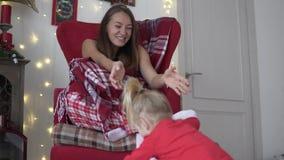 Молодая мать сидит в красном стуле Оно покрыто с теплым одеялом видеоматериал