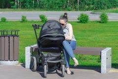 Молодая мать сидит на скамейке в парке и трясет pram r стоковое фото