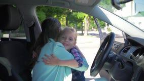 Молодая мать сидя в автомобиле встречает школьницу от школы после уроков и счастливо обнимать видеоматериал