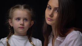 Молодая мать сидя с ее дочерью, оба с серьезными выражениями сток-видео