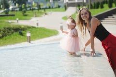 Молодая мать с дочерью на фонтане Стоковое Фото