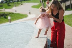 Молодая мать с дочерью на фонтане Стоковые Изображения