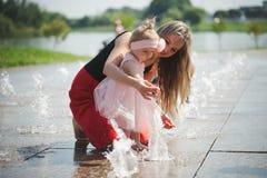 Молодая мать с дочерью на фонтане Стоковая Фотография RF