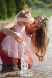 Молодая мать с дочерью на фонтане Стоковые Фото