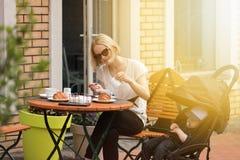 Молодая мать с ее годовалым ребенком в кафе улицы стоковые фотографии rf