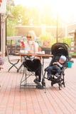 Молодая мать с ее годовалым ребенком в кафе улицы стоковое изображение