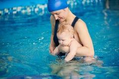 Молодая мать с ее младенцем во время первой попытки плавая в бассейне Плавать в бассейне для гармоничного развития младенцев стоковые фото