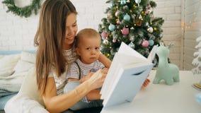 Молодая мать с молодым сыном читает книгу на таблице акции видеоматериалы